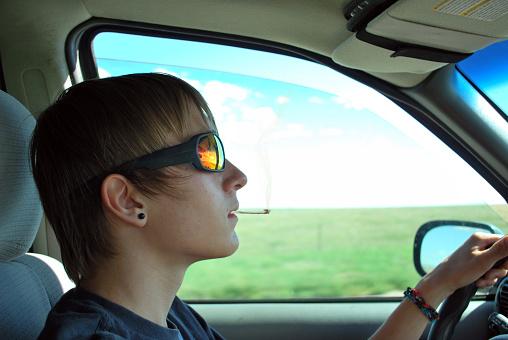 A teenage boy smoking a marijuana joint while driving.